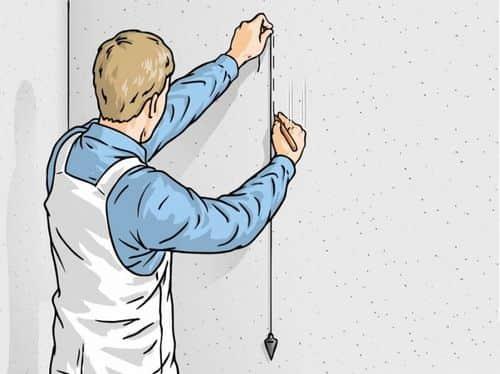 С помощью отвеса наносим вертикальную линию на стене